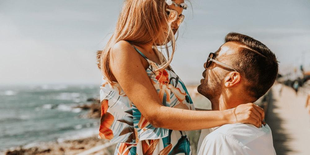 šťastný a spokojný pár na pláži, žena sa usmieva