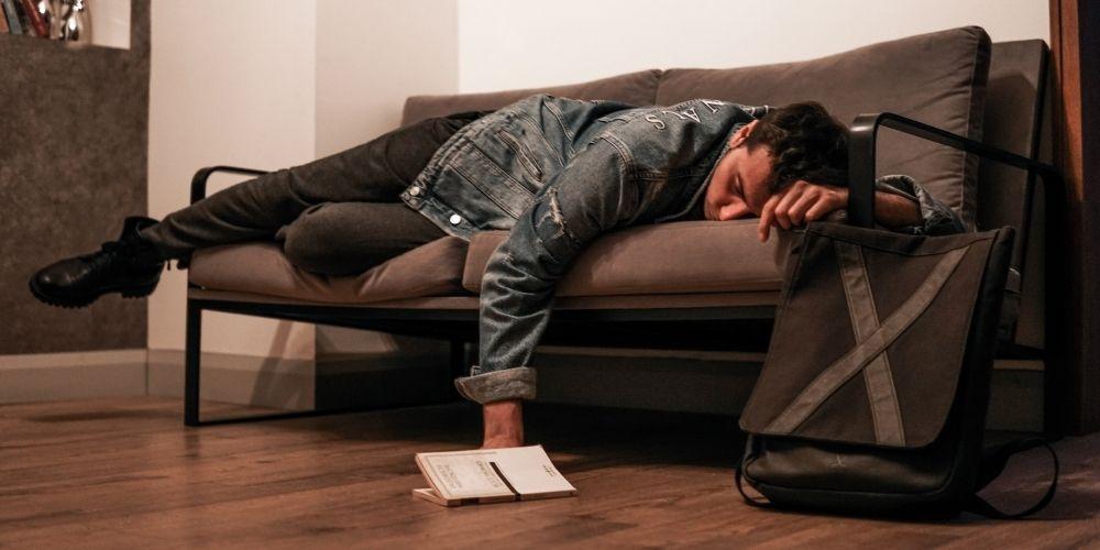 spiaci muž na gauči - únava, vyčerpanosť a slabosť môžu viesť k problémom s erektilnou dysfunkciou